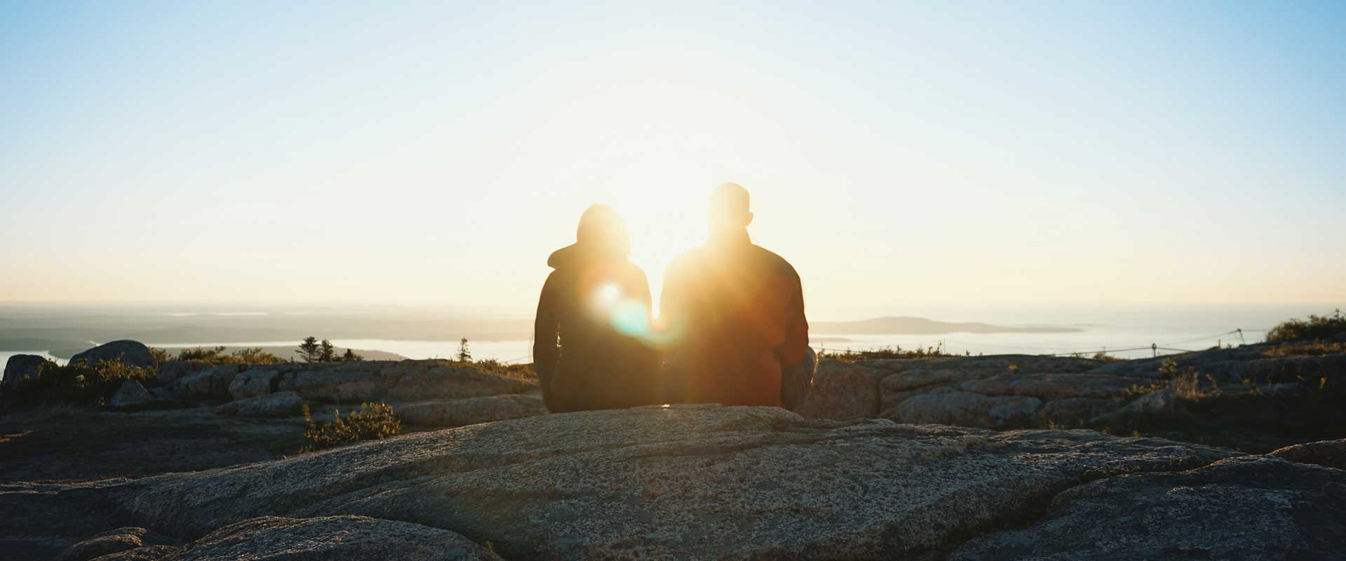 A couple sit side-by-side while enjoying a scenic landscape near the coast