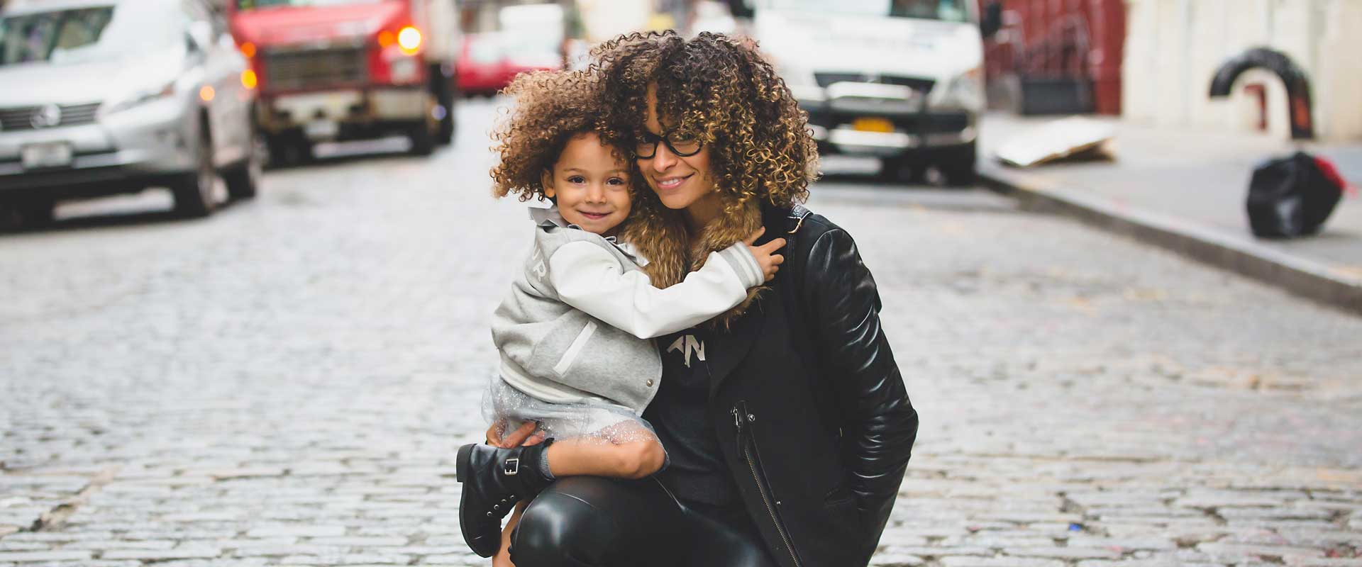 Young woman in black leather jacket holds female toddler wearing grey coat while crouching in an empty street