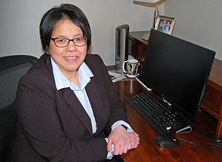 woman with black hair wearing glasses and suit at desk in front of computer