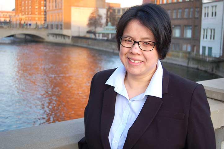 woman with black hair wearing glasses and suit on bridge